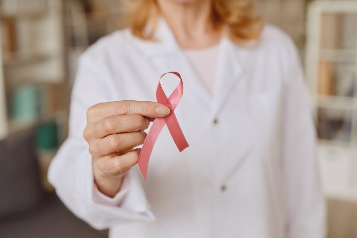 Female Doctor Holding Pink Ribbon for Breast Cancer Awareness